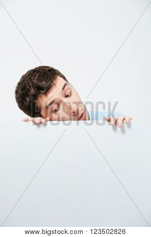 Young man peeking from blank board isolated on a white background