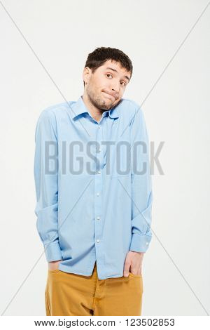 Portrait of a young man shrugging shoulders isolated on a white background