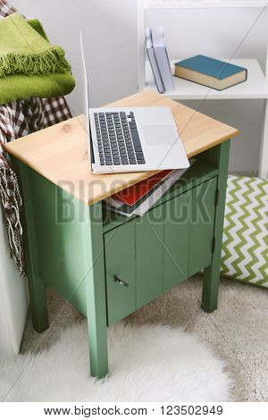 Nightstand with laptop in interior of living room