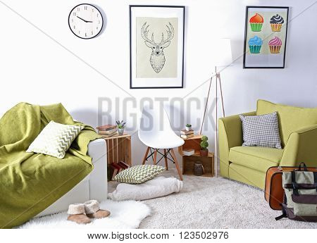 Interior of living room with green armchair and couch