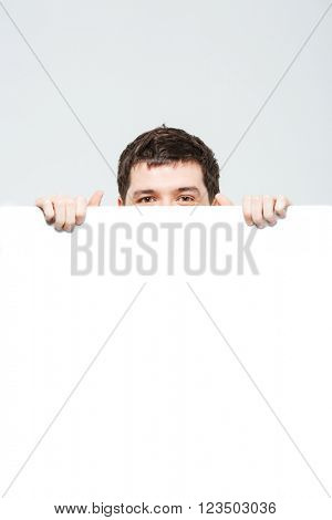 Man peeking from blank board isolated on a white background