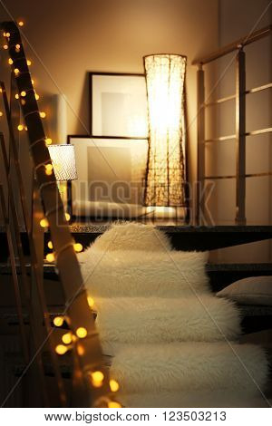 Modern stairs with electric garland, white furry bedspread and lamp