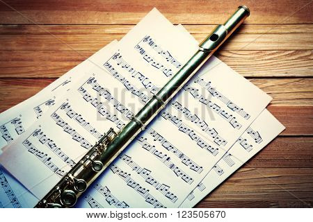 Flute on musical notes and on wooden table background