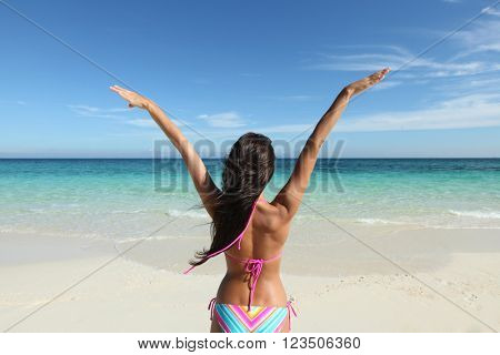 Happy woman with raised hands on beach