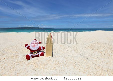 Santa Claus surfer on sand at tropical ocean beach, Christmas and New Year winter vacation concept