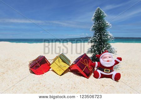 Santa Claus with fir tree and gifts on sand at tropical ocean beach, Christmas and New Year winter vacation concept