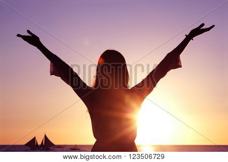 Woman with raised hands at sunset by the sea