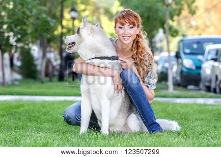 happy woman with his dog sitting on grass green in park