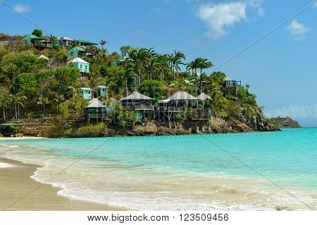 Tropical beach at Antigua island in Caribbean with white sand turquoise ocean water and blue sky