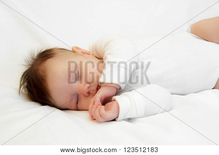 Little newborn girl slepping on a white background