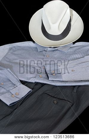 fedora hat collared button down shirt and dress slacks against black