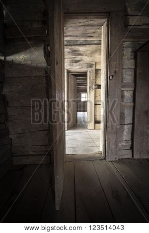 Hallway With Open Doors And Sunlight. Abandoned cabin with hallway and open doors encased in light. This is a historical structure in a national park and not a private residence.