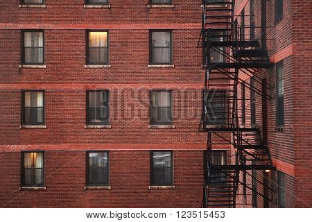 Brick backside of a city apartment building, with fire escape.