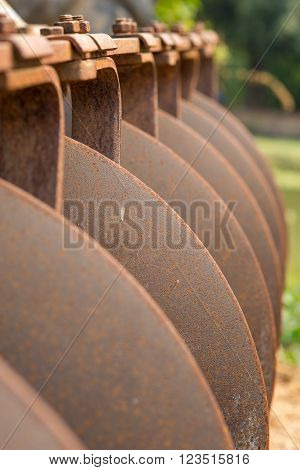 Close-up detail of an old tractor plough. Agriculture and farming concept.