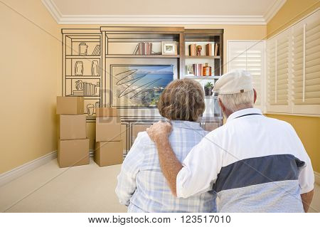 Senior Couple In Room With Moving Boxes Looking At Drawing of Entertainment Unit.