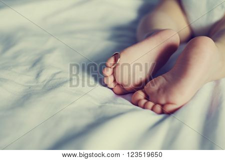 baby's feet with a golden ring on one of the toes, indoor shoot