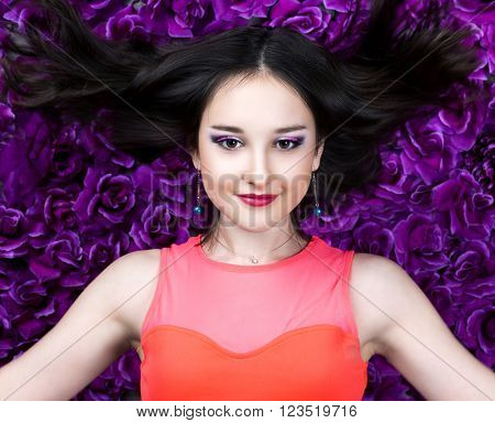 beautiful young brunette teenage girl   with makeup and flying long hair in the studio