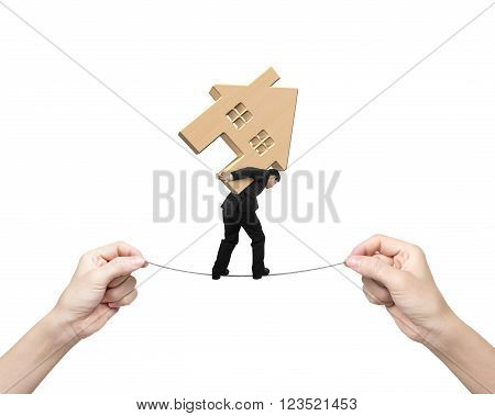 Man carrying wooden house and balancing on tightrope with two hands pulling, isolated on white background.