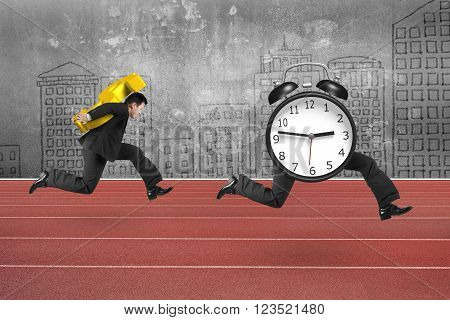 Man carrying dollar sign and running after alarm clock of running legs on red track with concrete wall background.