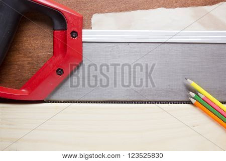 Toothed steel hand saw cutting through a new boards of wood left in position surrounded by wood chips with nobody in the frame in a DIY carpentry woodworking or joinery concept