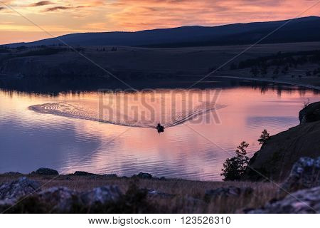 Dramatic red sunset over baikal lake with a sailboat and a redsky