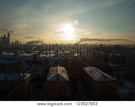 Sunrise over the city. Brightly lit only rooftops