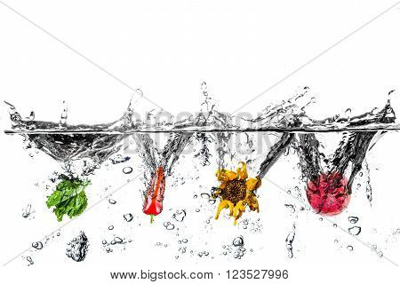 Water splashes with salad, pepper, sunflower and Garnet. Composite image of four subject and water splash and bubbles. White is clipping.