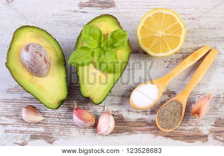 Avocado with ingredients and spices to avocado paste or guacamole garlic lemon basil concept of healthy food nutrition and omega fatty acids