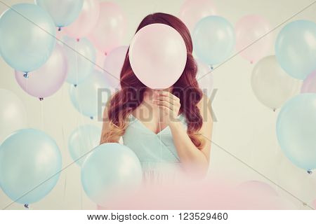 Young woman covering her face with pink balloon