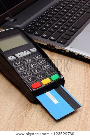 Payment terminal with credit card and laptop on wooden desk credit card reader paying using credit card finance and banking concept