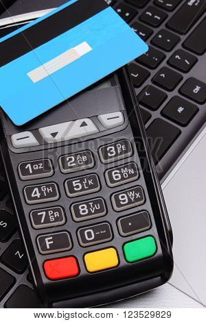 Payment terminal with contactless credit card and laptop, credit card reader, paying using credit card, finance and banking concept
