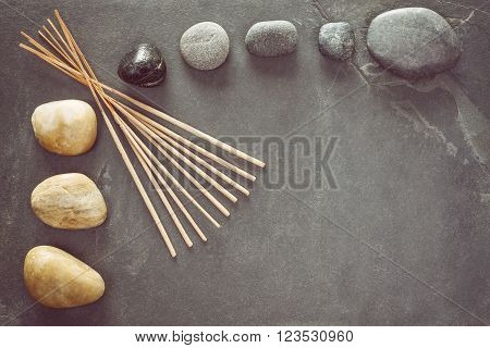 Retro Toned Stones On Slate Background With Incense Sticks.