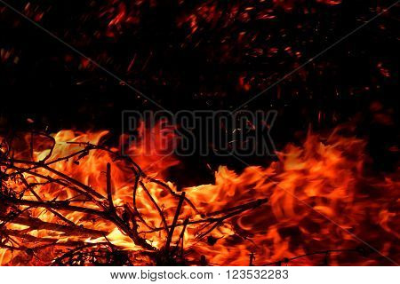 red hot blazing fire on black background with spakrs (the concept of risk of forest fires)