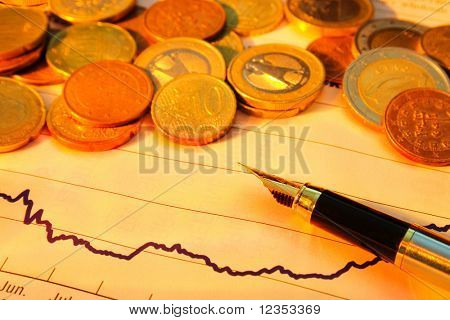 fountain pen and coins on the financial graph with warm yellow lighting
