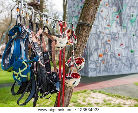 Helmets harnesses and protective gear near a climbing wall outdoors