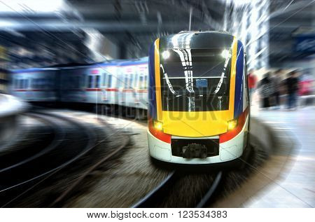 Fast moving train leaving station platform with motion blur