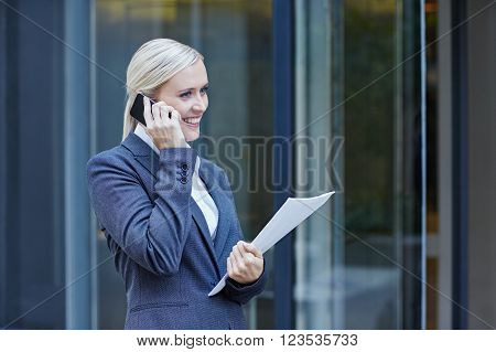 A young businesswoman talking on her cellphone outside