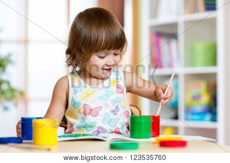 pretty kid girl painting with colours in kindergarten or playschool