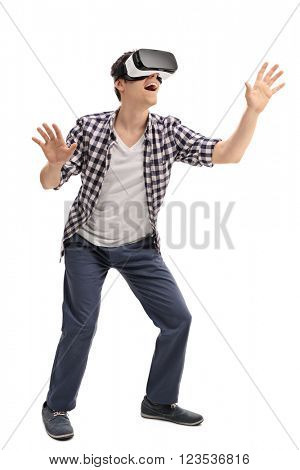 Full length portrait of  young excited man experiencing virtual reality isolated on white background