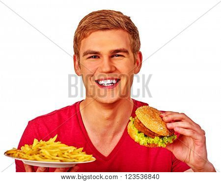 Young man eating fast food big hamburger and fried potatoes. Fastfood concept.