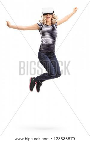 Vertical shot of a young joyful woman experiencing virtual reality and jumping shot in mid-air isolated on white background