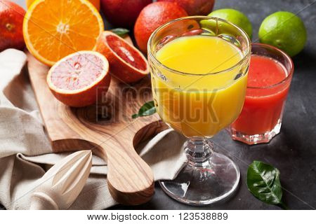 Fresh citruses and juices on dark stone background. Oranges and limes