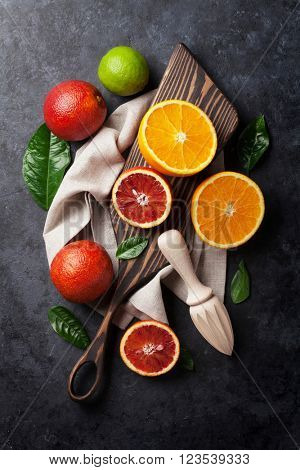 Fresh citruses on dark stone background. Oranges and limes. Top view