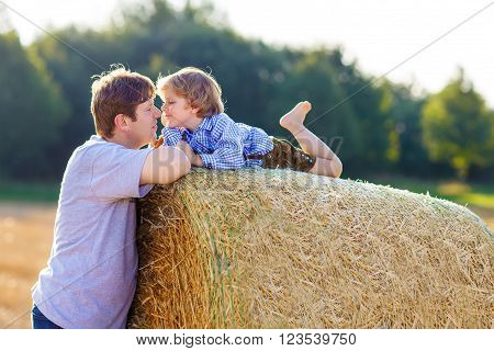 Happy family of two: Young father and his little son having fun on yellow hay field in summer. Funny kid boy and young man enjoying summertime ** Note: Soft Focus at 100%, best at smaller sizes