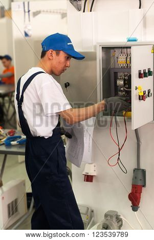Tyumen, Russia - March 24. 2016: Open championship of professional skill among youth. World skills Russia Tyumen - 2016. Young electrician performs a task of professional competition