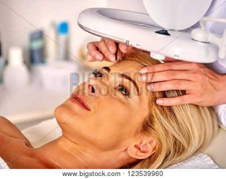 Woman middle-aged in spa salon with young beautician. Tweezing eyebrow by beautician. Aesthetic medicine.