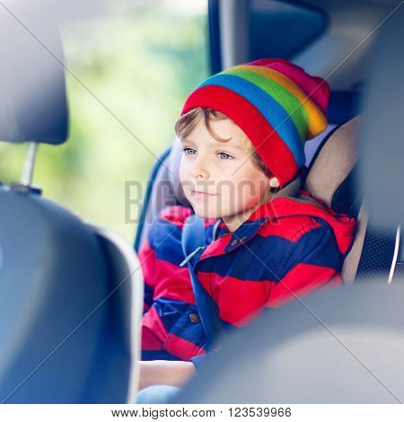 Adorable cute preschool kid boy sitting in car. Child in safety car seat with belt. Safe travel with kids and traffic laws concept.