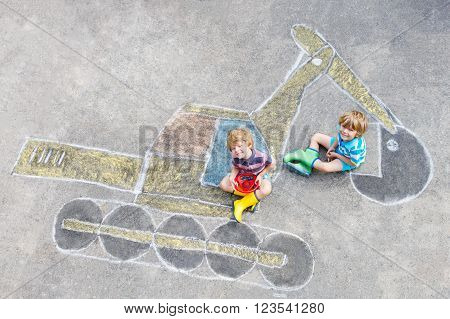 Two little happy kid boys having fun with excavator picture drawing with colorful chalk. Creative leisure for children outdoors in summer.