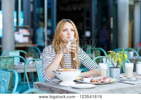Young beautiful woman drinking champagne with milk and having healthy breakfast in outdoor cafe in summer city in Europe.