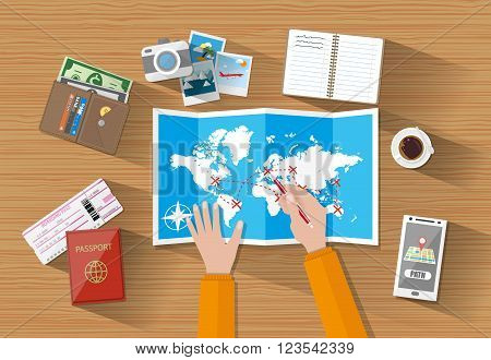 cartoon mans hands at table with paper map of world and tourist equipment. passport, airplane ticket, coffee cup, notebook, smartphone with navigation application, photo camera photos, wallet. vector illustration in flat design on wooden background